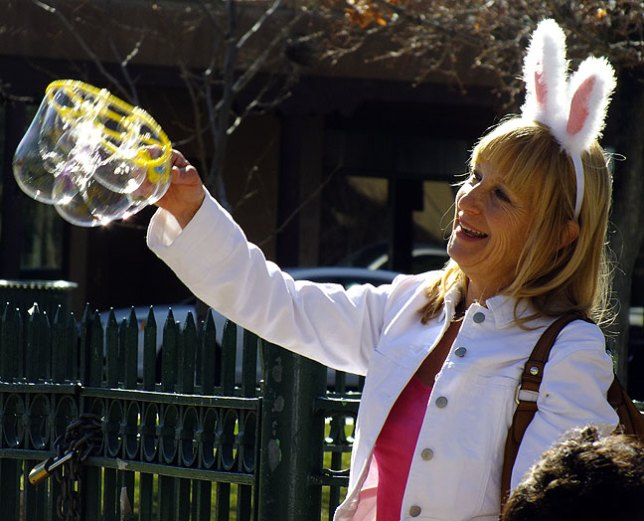 A woman wears bunny ears for Easter as she creates bubbles on The Plaza in Santa Fe.