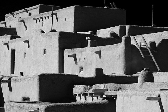 This bold black-and-white rendition of the main structures at Taos Pueblo emphasize its linear construction. Compare to...
