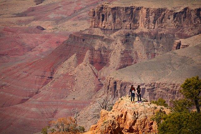 Visitors climb on a precipice at Grand Canyon's Desert View.