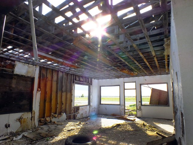 Sunlight streams through the broken, falling-down roof of the filling station at the Plague Town.