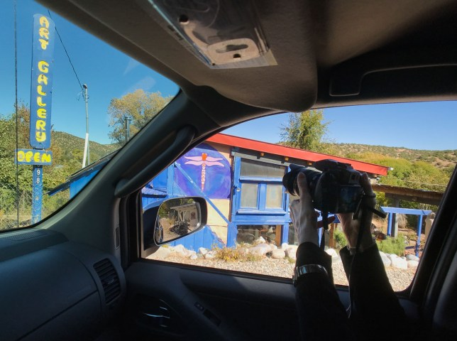 Abby pokes her camera out the passenger side window to photograph an art gallery in Cundiyo, New Mexico.