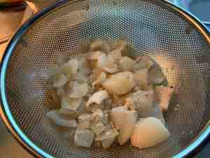 Cooked onions in colander