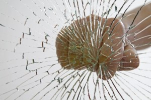 Fist shattering glass pane.