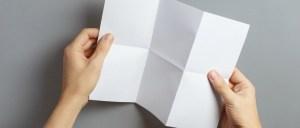 Hands folding a piece of paper.
