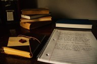 Spiral notebook and books on desk.