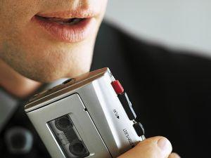 Man speaking into tape recorder.