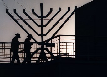 As the sun sets into the ocean behind them, Rabbi's Shneur Zalamon Lipskier (cq), left, and Mendel Loschak make their way past a ten-foot high by twelve-foot wide menorrah before a lighting ceremnony to celebrate the first night of Hanukkah, tuesday evening on the Santa Monica Pier. The two are form the Chabad House of Lubavitch headquarters in Brooklyn, New York. STAFF PHOTO BY RICHARD HARTOG 12/23/97