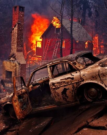 A burnt out car sits in the foreground as an entire neighborhood burns to the ground, Wednesday afternoon along Hook Creek Road in the Cedar Glen area of Lake Arrowhead.
