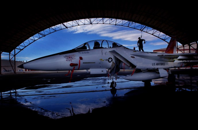 Airman First Class (A1C) Michael Vratanina (cq) is silhouetted against a bright blue sky as he cleans an F15B Eagle in a wash rack, Thursday afternoon at Edwards Air Force Base.