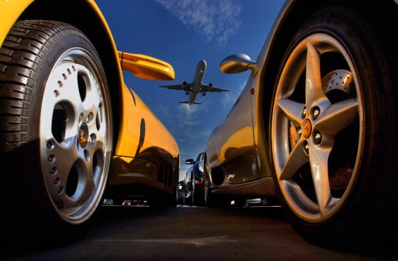 An airplane making a landing is framed by a bright yellow Lamborghini on the left, and a Ferrari, right, at Beverly Hills Rent A Car, Friday morning near LAX in Los Angeles. Curbside service is offered, and many clients are picked up at the airport.