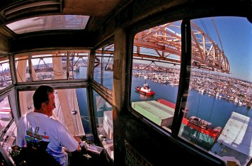 Longshoreman Greg Mitre in his crane unloading cargo, works high above the port,Wednesday morning at Long Beach Harbor. The supersizing of the ports. Both Los Angeles and Long Beach are opening ther first so-called mega-terminals this year, and each have ordered up a dozen of the world s largest cranes to operate on them. The Gerald Desmond Bridge is slated to be replaced with a new one that will rival the Golden Gate in size. All this in anticipation of arrival of mega-freighters, twice as big as any on the ocean today.