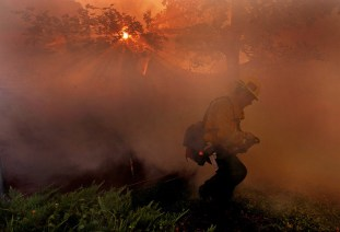 The early sun pokes through the trees as firefighter Juan Mota of San Bernardino 38 turns away from the smoke as he fights a house fire on Secret Dr. in Running Springs near Lake Arrowhead Tuesday morning October 23, 2007.