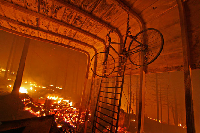 A bike hanging in the shell of a carport can be seen as wildfire rages through homes along Circle View Drive in Running Springs near Lake Arrowhead early Tuesday morning October 23, 2007.