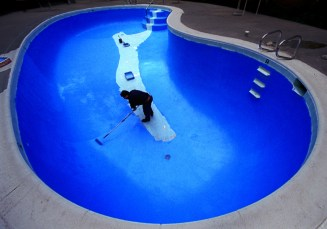 In Too Deep?: Using a trail of the old paint underneath and behind him, head maintenance man Jose Valerano finds himself in the deep end of a pool as he works his way backwards while repainting the pool's bottom a bright blue at a motel (the Lincon Inn), recently in Anaheim.