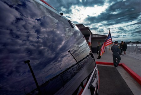 Clouds are reflected in a new Harbor Patrol vehicle window, left, as Deputy Sheriff color guard Montoya walks with a flag before the start of the grand opening ceremony for the newly completed Harbor Patrol Rescue Operations Center, Thursday morning in Corona del Mar. The 7,200-square-foot facility replaced the former 40-year-old Harbor Patrol Headquarters.