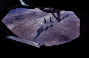 Looking through the window at the refueling pad of a KC-135 Stratotanker, an F-15 fighter jet peels off after fueling near the skies over Salt Lake City, Utah.