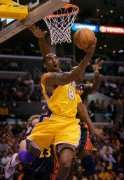 Laker Kobe Bryant leaves Golden State Warriors Mike Dunleavy, bottom left, and Adonal Foyle behind as he scores on a reverse layup during first quarter at the Staples Center, Tuesday, April 11, 2006.
