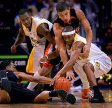 Cal Bear Ayinde Ubaka (cq) has the inside track on a loose ball as he battles Oregon St. Beavers Michael Johnson, top, and Marcel Jones, left, during first half of first round game of the Pac 10 Basketball Tournament at the Staples Center in Los Angeles, Wednesday March 07, 2007. Cal's Patrick Christopher is at left.