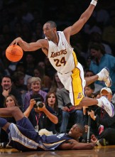 Memphis Grizzlies Hakim Warrick, bottom, can only watch from the floor as Laker Kobe Bryant saves the ball from going out and maintains possession during fourth quarter at the Staples Center Sunday in Los Angeles November 12, 2006.