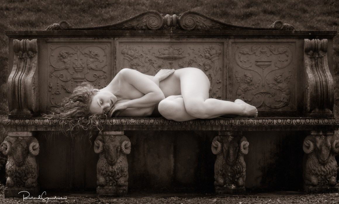 july print of the month is a monochrome image featuring a figure study of model ivory flame lying across a stone bench which is supported by four rams carved in stone