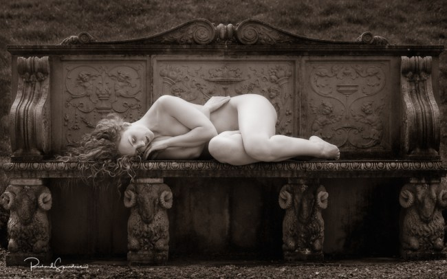 Fine art nude resting on the stone bench