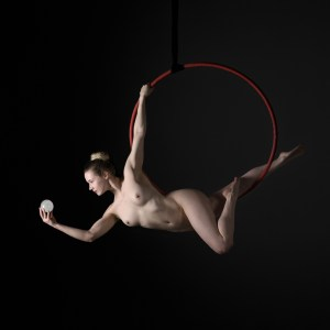 Aerial Arts photographer - Aerial hoop photographer - Aerial Arts photography - aerial artist using a red aerial hoop to hold a dynamic pose at the bottom of the hoop holding a white orb against a black backgrounda black background