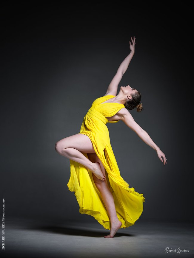 Dance Photographer - Dance photography - colour dance image of dancer ariel taylor wearing a yellow dress and reaching up with dynamic dance move shapes from the dress