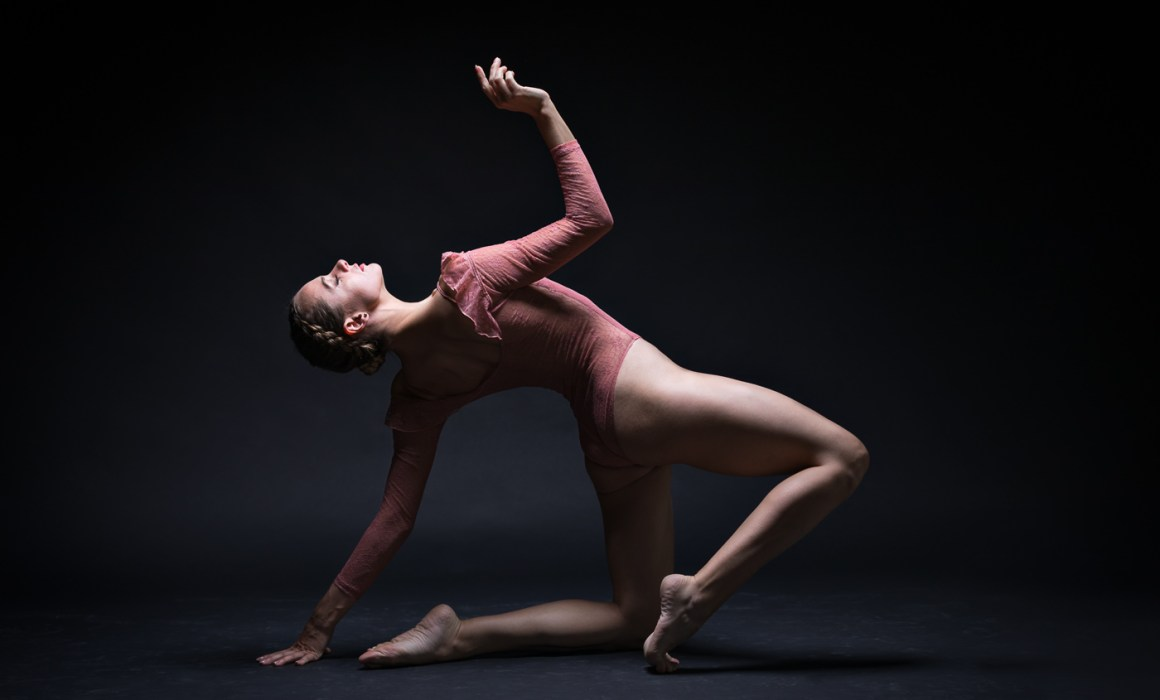 a colour image of dancer alya rose with bent legs and leaning back on her left arm with her right reaching up towards the light