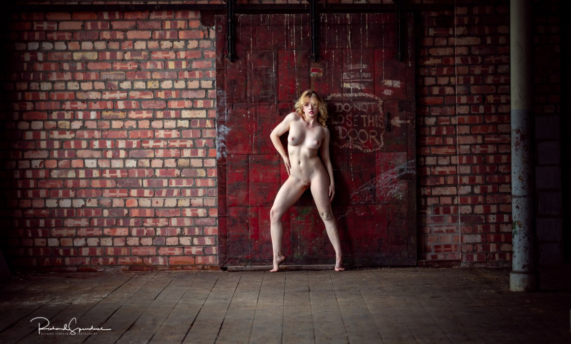 artistic nude model nicole rayner posing against a red steel door in an old mill location