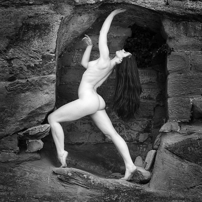 november print of the month is a monochrome figure study of the model elle beth in a sandstone rock opening itled rough and smooth