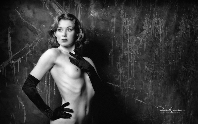 monochrome image of the model wearing just black gloves