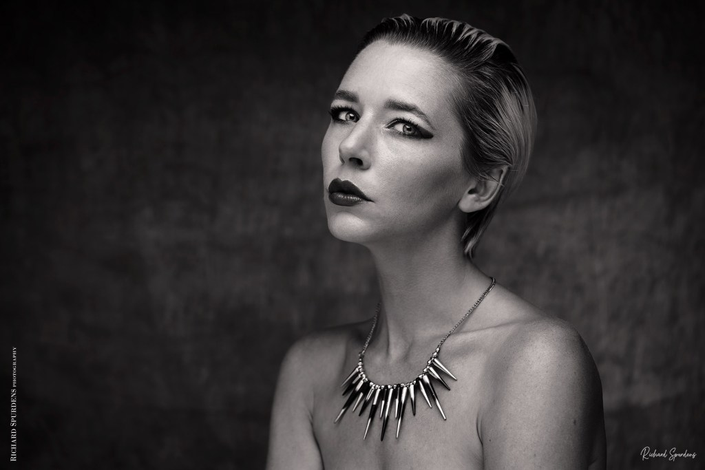 monochrome image from virtual shoot with amie boulton head and shoulders shot with model wear a spiky necklesss