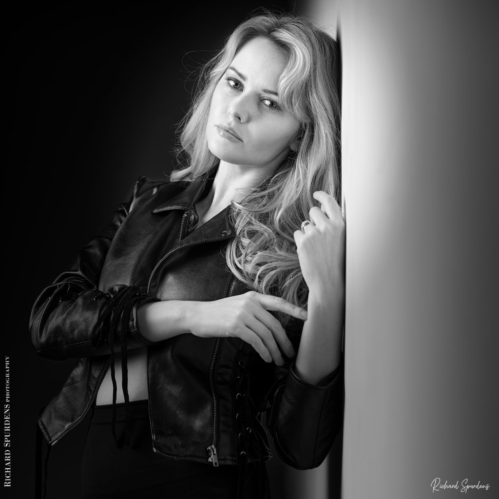 Fashion Photography - Fashion Photographer - monochrome image of carla in her leather jacket leaning against the wall looking at the viewer