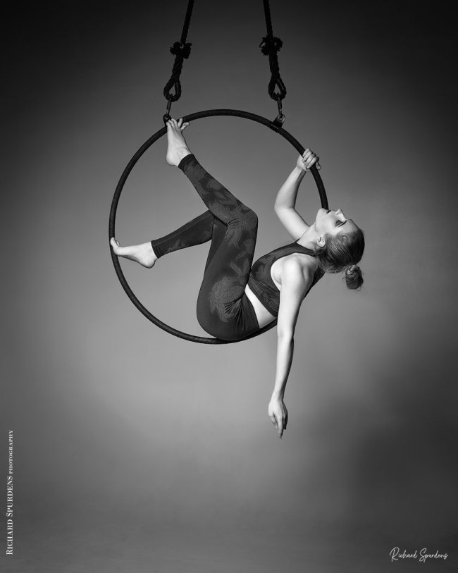 Aerial Arts photographer - Aerial hoop photographer - Aerial Arts photography - Aerial hoop photography - monochrome image featuring aerialist ariel taylor sitting inside her aerial hoop holding position with feet and back