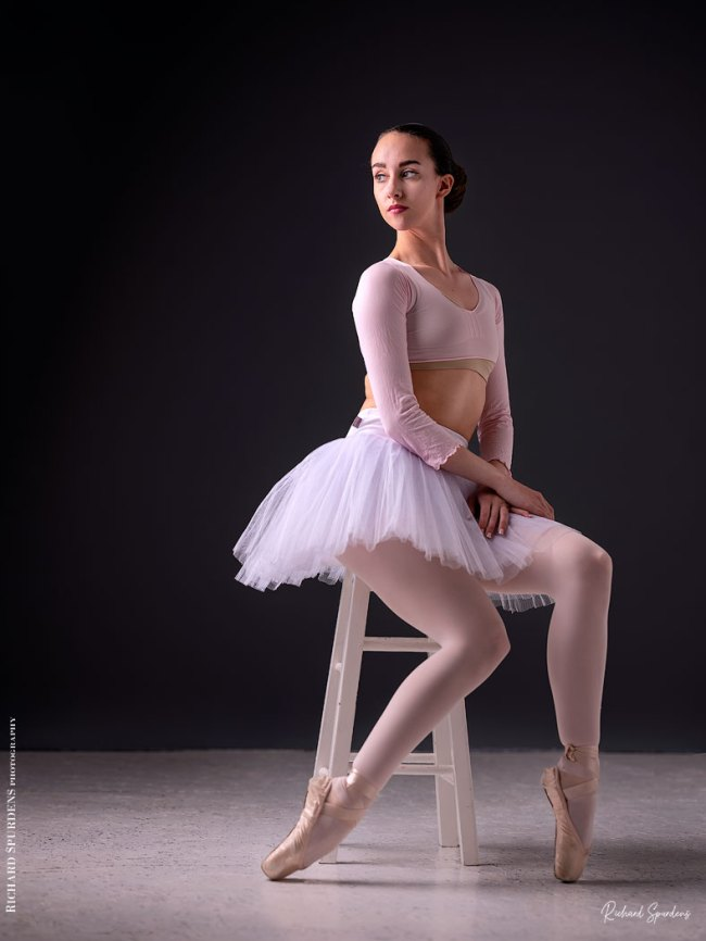 Dance Photographer - Dance photography - colour image of dancer Erica Mulkern seated on a stool wear a white tute and looking back to wards the light