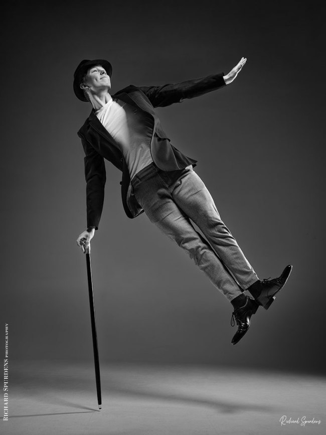 Dance Photographer - Dance photography - monochrome image featureing dancer hamish using a cane to jump into the air and hold a charile chaplin pose