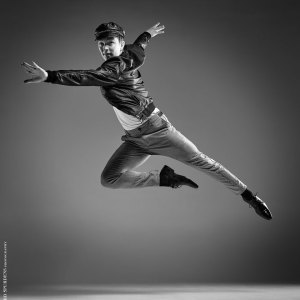 Dance Photographer - Dance photography - monochrome image of male dancer making a leap across the image wearing a leather jacket and cap based on a west side story idea