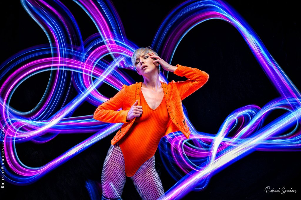 Fashion Photography - Fashion Photographer - colour image of model wearing orange jackets and body lighting swirls around the model using blues and purple lights wands around the model