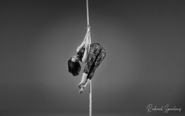 aerial arts photography - aerial arts photograher - monochrome image of aerial artist working with a hanging rope, she is holding the pose with her hands and arms above her head is angled down and she is holding her legs together angled across the front of the rope