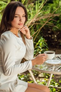 Brunette in white drinking coffee outdoors 2