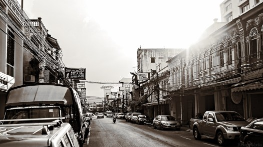 A view down Phang Nga Road in Phuket Town in black and white with the sun setting behind the building to the right.