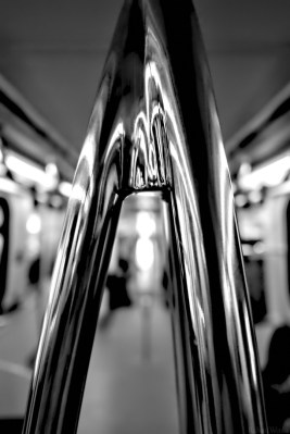 Reflections on a handhold in a subway train