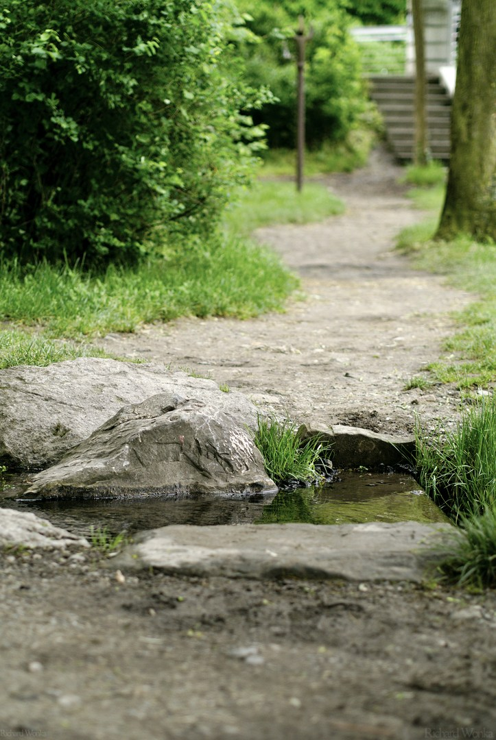 A path through a park, crossed and interrupted by a rocky creek