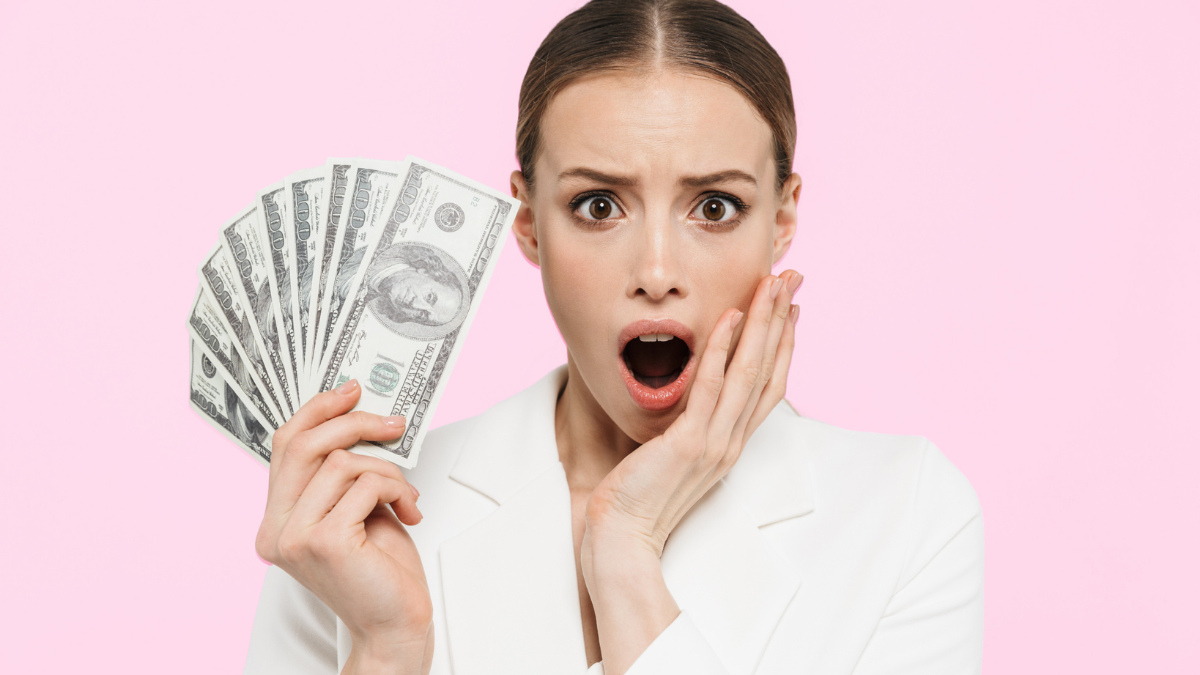 woman shocked at paying lower taxes holding money fan