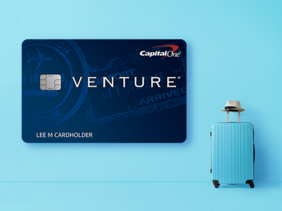 capital one venture card next to blue suitcase