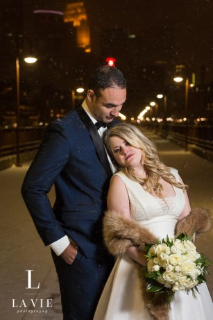 married couple with white wedding bouquet in winter