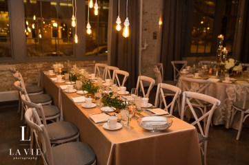wedding reception table with greenery decor and lights