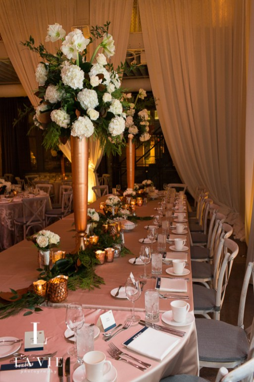 tall white centerpiece in copper vase
