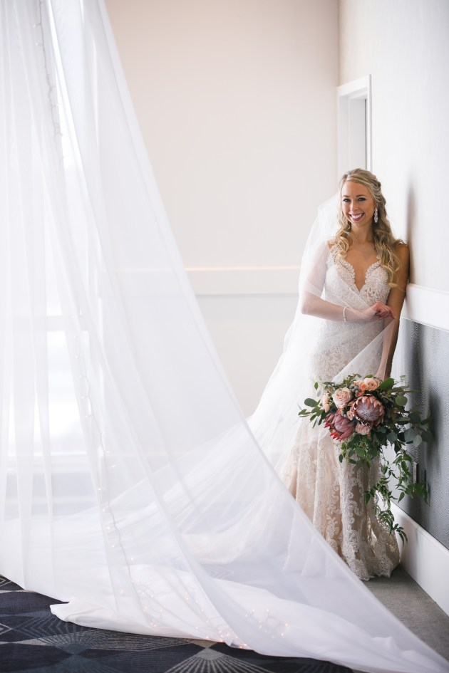 bride with drapery and wedding bouquet