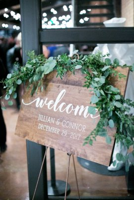 wooden welcome sign with greenery at wedding reception